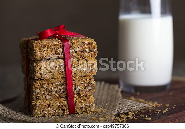 Stack of oatmeal crunchy cookies and milk in background - csp49757366