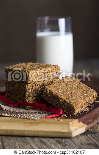 Stack of oatmeal crunchy cookies and milk in background - csp51162107
