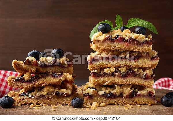 stack of square slices of baked crumble pie with blue plum on a wooden board - csp80742104