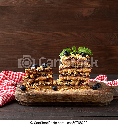 stack of square slices of baked crumble pie with blue plum on a wooden board - csp80768209
