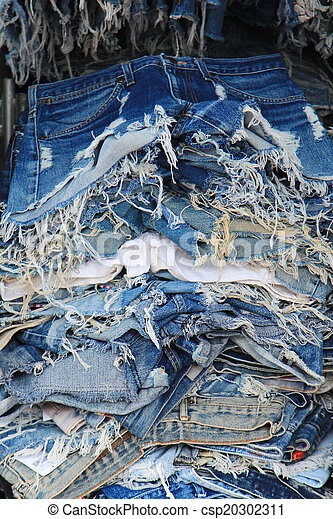 Stack of torn old jeans - csp20302311