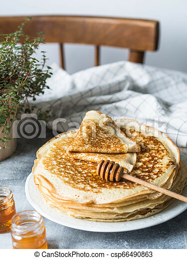 Stack Russian homemade yeast pancakes on white plate, wood honey spoon and honey in jars on table. Traditional wheat pancakes for Shrovetide. - csp66490863