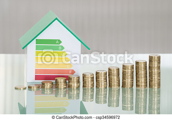 Stacked Coins And House Model Showing Energy Efficiency Rate - csp34596972
