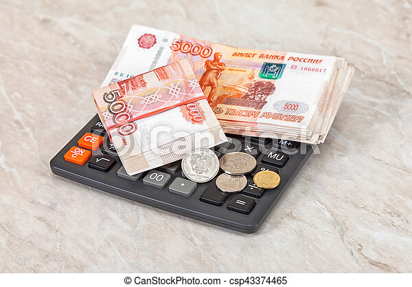Stacks of five thousandths banknotes of russian roubles, coins and calculator - csp43374465
