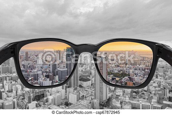 Blick durch die Brille auf den Stadtblick in Sonnenuntergang. Farbblindheitsbrille, Smart-Glas-Technologie - csp67872945