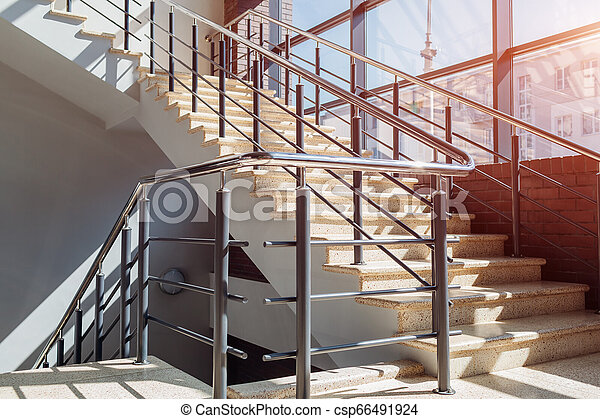 Staircase in modern buisness center building. Emergency exit. Stairs in shopping center. White ladder by window - csp66491924
