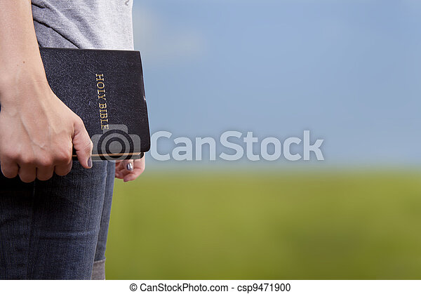 Standing Holding the Bible in a Field - csp9471900