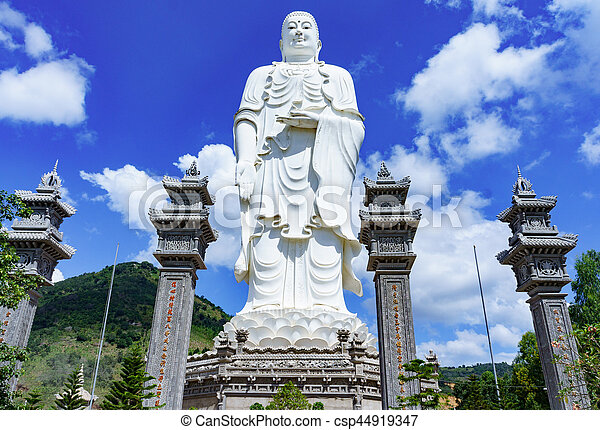 standing white Buddha on a background of blue sky - csp44919347