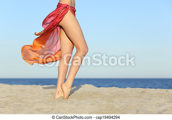 Standing woman legs posing on the beach wearing a pareo - csp19494294