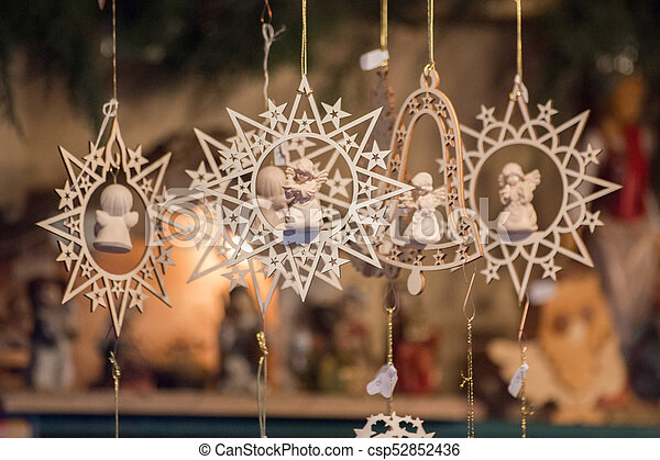 Star shaped and bell shaped wooden Christmas ornaments with small angels - csp52852436