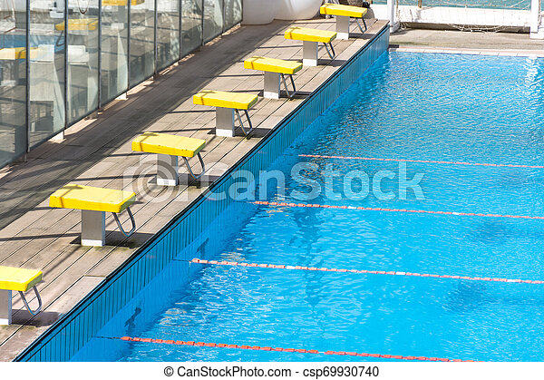 Starting blocks, jump platform in row by the swimming pool.