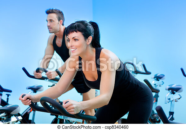 Stationary spinning bicycles fitness girl in a gym - csp8340460