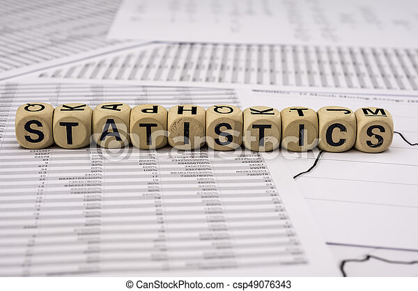 Statistical analysis sheets with the word statistics assembled with wooden letter blocks - csp49076343
