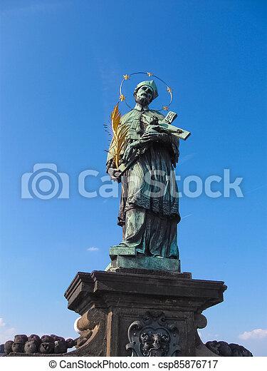 Statue of St. John of Nepomuk on the Charles bridge in Prague, Czech republic. - csp85876717