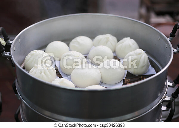 steamed chinese buns in silver steamer in the market
