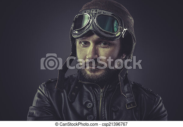 steampunk pilot dressed in vintage style leather cap and goggles - csp21396767
