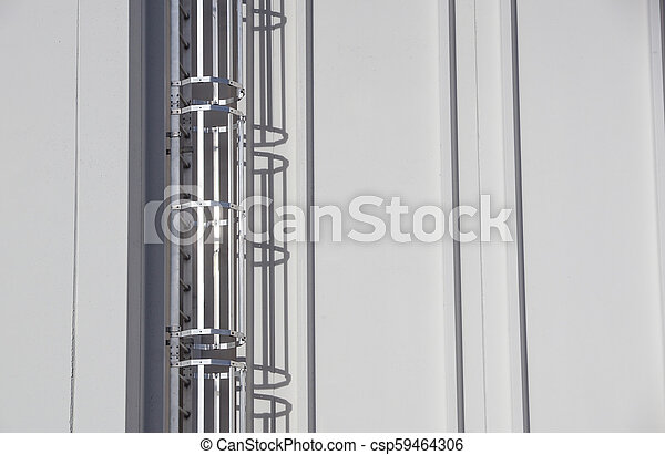 Steel ladder with protection, attached to an industrial, production hall or building. - csp59464306
