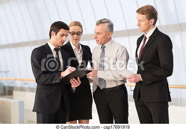 Sie brauchen alle einen Rat. Vier Geschäftsleute diskutieren etwas, während sie sich nahe stehen - csp17691919