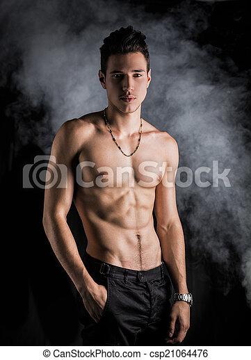 stehende , athletische, shirtless, mager, junger, dunkler hintergrund, mann - csp21064476