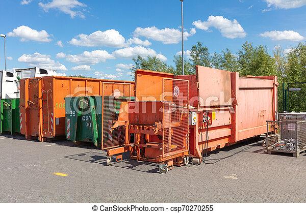 Orangene Abfallverdichter stehen auf einem Fabrikgelände mit anderen Abfallbehältern neben ihnen - csp70270255