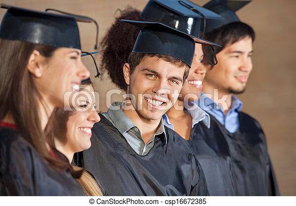 Ein glücklicher Mann, der am Schulabschlusstag mit Schülern steht - csp16672385