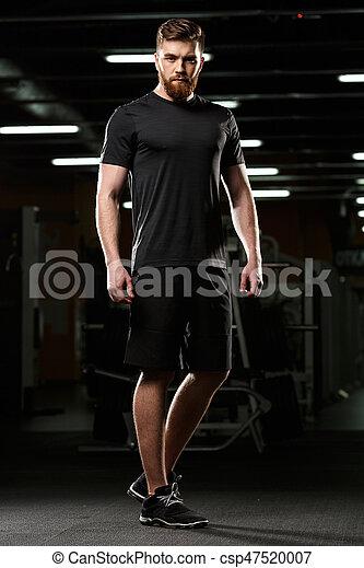 Ernster, gutaussehender Sportmann steht und posiert in der Turnhalle - csp47520007