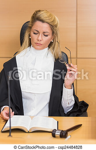 Stern judge reading her notes  - csp24484828