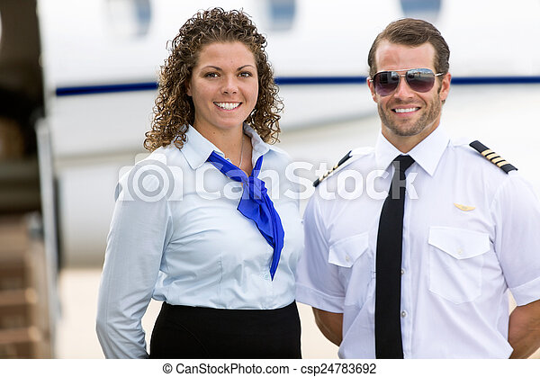 Stewardess And Pilot Standing Against Private Jet - csp24783692