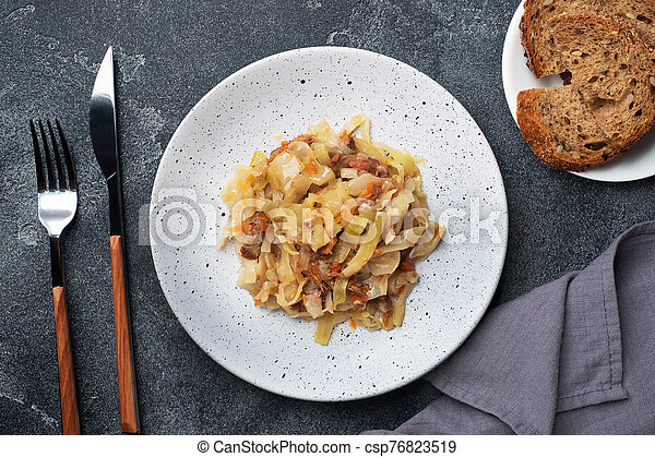 Stewed cabbage with meat on a plate. Dark concrete background. - csp76823519