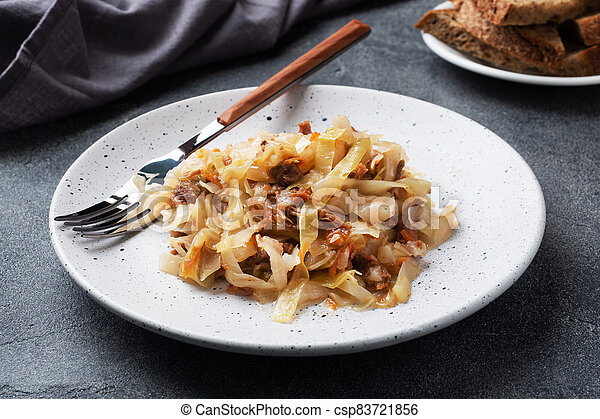 Stewed cabbage with meat on a plate. Dark concrete background. - csp83721856