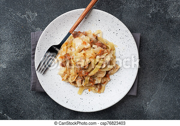 Stewed cabbage with meat on a plate. Dark concrete background. - csp76823403