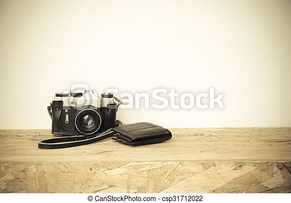 still life photography : old and dusty camera and wallet on space of old wood in vintage color tone - csp31712022