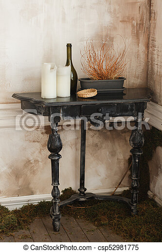 Still-life with an old black wooden table, candles in dirty room corner - csp52981775
