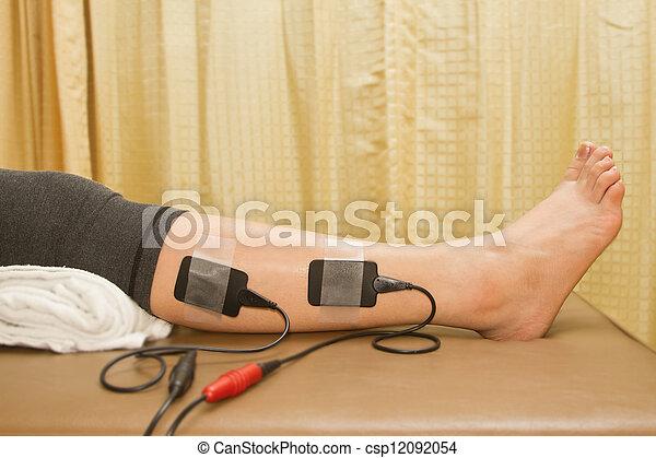 Terapia física, mujer con estimulador elétrico para aumentar la fuerza muscular y liberar el dolor - csp12092054