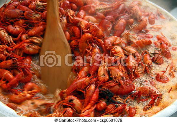 Stirring boiling crawfish with a small boat paddle. - csp6501079