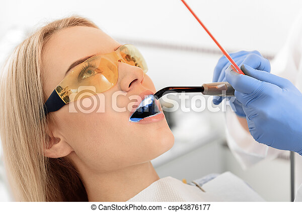 Stomatologist examining mouth of young woman - csp43876177