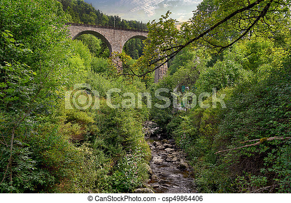 stone arch train trestle over creek - csp49864406