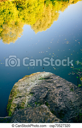 Stone in front of the forest lake - csp70527320