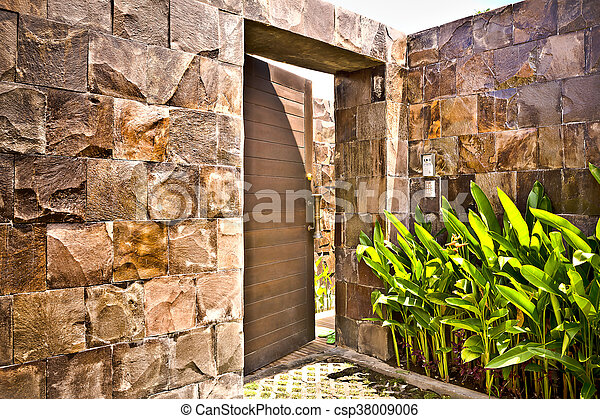 Stone wall entrance to a modern mansion
