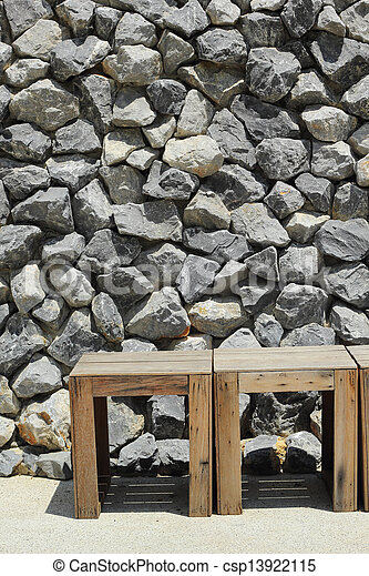 Stone wall with a chair. - csp13922115