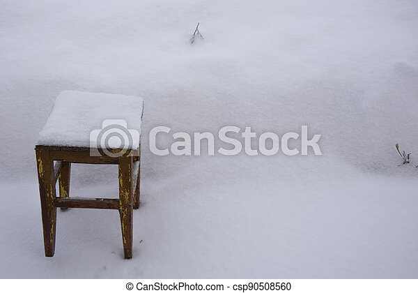 Stool in a snowdrift. Old wooden chair in the snow. There is a lot of snow in the garden in winter. - csp90508560