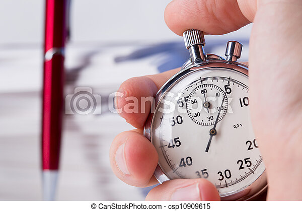 Stopwatch in hand on background of paper cards - csp10909615
