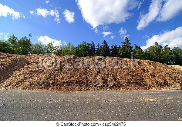 storage of wooden bio fuel against blue sky - csp5462475