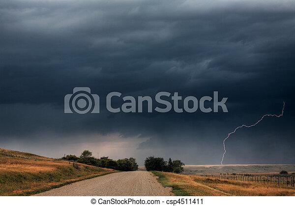Storm clouds and lightning along a Saskatchewan country road - csp4511411