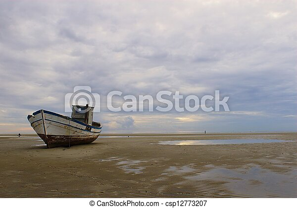 Stranded fishing boat after a storm on the beach at Grado, Italy - csp12773207