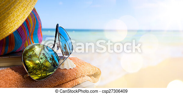 Straw hat, bag and sun glasses on a tropical beach - csp27306409