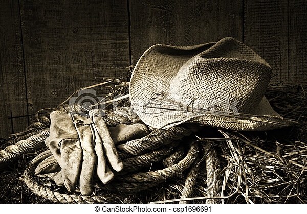 Straw hat with gloves on a bale of hay - csp1696691