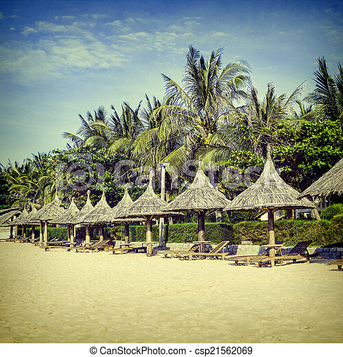 Straw sunshades and chaise longue on the tropical beach. - csp21562069