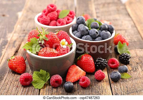 strawberry, blueberry and raspberry on wood background - csp47487263