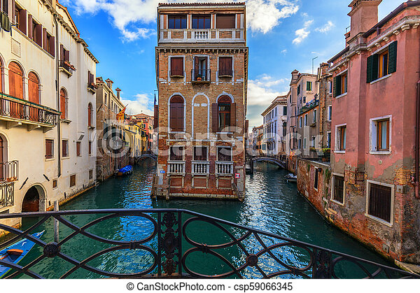 Street canal in Venice, Italy. Narrow canal among old colorful brick houses in Venice, Italy. Venice postcard - csp59066345